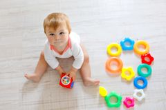 Adorable baby girl playing with educational toys in nursery. Happy healthy child having fun with colorful different toys stock photos