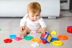 Adorable baby girl playing with educational toys in nursery. Happy healthy child having fun with colorful different toys royalty free stock photography