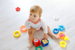 Adorable baby girl playing with educational toys in nursery. Happy healthy child having fun with colorful different toys royalty free stock photo