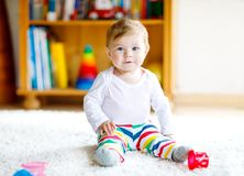 Adorable baby girl playing with educational toys in nursery. Happy healthy child having fun with colorful different toys. At home. Baby development and first stock photo