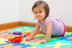 Adorable baby girl playing on floor Royalty Free Stock Image