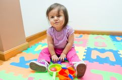 Adorable baby girl playing on floor mats Stock Photography
