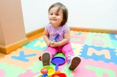 Adorable baby girl playing on floor mats Stock Image