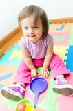 Adorable baby girl playing on floor mats Royalty Free Stock Image