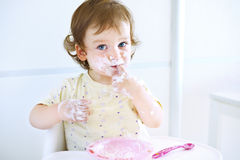 Adorable baby girl playing with food. Child eating yogurt. Dirty face of happy kid. Portrait of a baby eating with a stained face. Royalty Free Stock Images