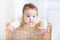 Adorable baby girl playing in a laundry Stock Images