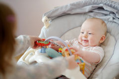 Adorable baby girl playing with older sister Stock Photos