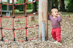 Adorable baby girl playing outside. Outdoor portrait of adorable baby girl having fun on playground, cute little 9-12 months child playing outdoors Royalty Free Stock Images