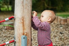 Adorable baby girl playing outside. Outdoor portrait of adorable baby girl having fun on playground, cute little 9-12 months child playing outdoors Royalty Free Stock Photos