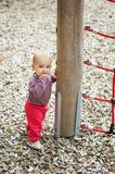 Adorable baby girl playing outside. Outdoor portrait of adorable baby girl having fun on playground, cute little 9-12 months child playing outdoors Stock Images