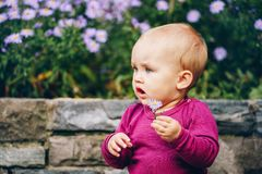 Adorable baby girl playing outside. Outdoor portrait of adorable 9-12 month old baby girl playing with purple flowers Stock Images