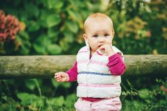 Adorable baby girl playing outside. Outdoor portrait of adorable baby girl of 9-12 months old playing in the park, wearing white bodywarmer Stock Photo
