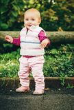 Adorable baby girl playing outside. Outdoor portrait of adorable baby girl of 9-12 months old playing in the park, wearing white bodywarmer Stock Photography