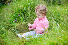 Adorable baby girl playing with a snail in the garden. Among beautiful flowers Royalty Free Stock Photos