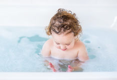 Adorable baby girl playing with soap foam in bath tub Stock Photos