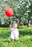 Adorable baby girl with red balloon in blooming garden Royalty Free Stock Photos