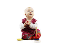Adorable baby girl in red clothes playing with some toys. Shot of an adorable baby girl in red clothes playing with some wooden toys stock images