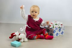 An Adorable Baby Girl in red dress playing with Christmas Gifts. Stock Photos