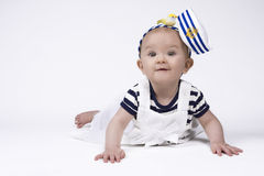 Adorable baby girl in sailor clothes. Beautiful baby girl wearing a sailor outfit and smiling Royalty Free Stock Image