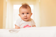 Adorable baby girl with serious face looks at the camera Royalty Free Stock Photography