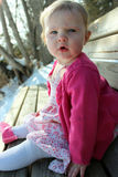 Adorable baby girl sitting on bench. Adorable little girl sitting on a bench on a warm winter day Royalty Free Stock Images