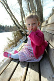 Adorable baby girl sitting on a bench Stock Images