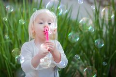 Adorable Baby Girl Sitting On Bench Having Fun Blowing Bubbles. Adorable Little Girl Sitting On Bench Having Fun With Blowing Bubbles Outside Stock Photos