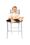 Adorable baby girl sitting on a chair Stock Images