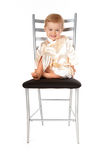 Adorable baby girl sitting on a chair Stock Photos