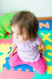 Adorable baby girl sitting on knees Stock Images