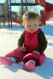 Adorable baby girl sitting by a park. Adorable baby girl sitting in the snow near a park Royalty Free Stock Images