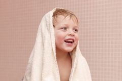Adorable baby boy sitting under a hooded towel after bath. stock images