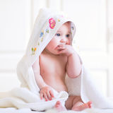 Adorable baby girl sitting under a hooded towel after bath Stock Photography