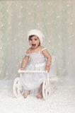Adorable baby girl sitting in a wooden Christmas snow sleigh, st Royalty Free Stock Image