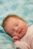 Adorable Baby Girl Sleeping on the Day She Was Born. An adorable baby girl sleeps on the day she was born. Eyes closed towards the viewer, good head of dark hair Stock Photography