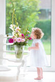 Adorable baby girl smelling beautiful flowers Stock Images