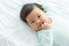 Adorable baby girl sucking thumb on the bed. This is growth develop behavior Royalty Free Stock Photography