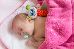 Adorable baby girl with toy covered with blanket Royalty Free Stock Photos