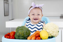Adorable baby girl with vegetables on chair. Adorable baby girl smiling and sitting on baby chair with vegetables in the kitchen Royalty Free Stock Photos