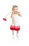 Adorable baby girl walking with flower in mouth stock photo