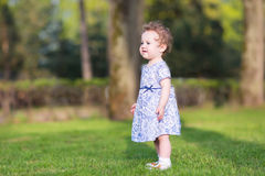 Adorable baby girl walking in the garden Stock Images