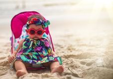 Adorable Baby Girl Wearing Sunglasses and Headband Sitting On A royalty free stock photo