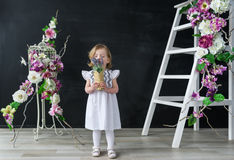 Adorable baby girl wearing a white dress smelling beautiful flowers Stock Photo