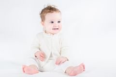 Adorable baby girl wearing white sweater sitting and playing Royalty Free Stock Photography