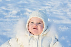 Adorable baby girl in a white jacket sitting outside on a sunny winter day Royalty Free Stock Photography