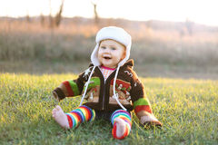 Adorable Baby Girl in Winter Hat and Sweater Laughing Outside. An adorable 8 month old baby girl with bright blue eyes is laughing while bundled up in a winter Royalty Free Stock Photo