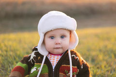 Adorable Baby Girl in Winter Hat and Sweater Outside. An adorable 8 month old baby girl with bright blue eyes is looikng at the camera while bundled up in a Royalty Free Stock Photography
