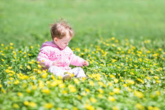 Adorable baby girl with yellow flowers in park Stock Images