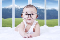 Adorable baby with glasses on bed Royalty Free Stock Photos