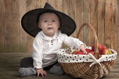 Adorable baby with halloween hat and apples. Adorable baby with halloween hat and basket full of apples Stock Images